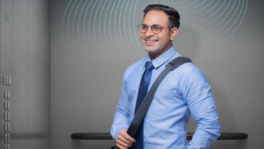 man with shoulder bag in elevator